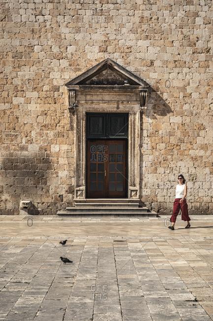 Croatia- Dubrovnik- Woman walking in front of old stone building