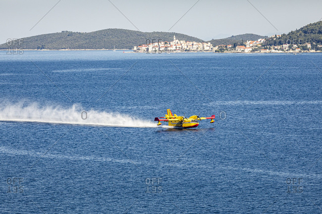 Firefighting airplane collecting water from sea