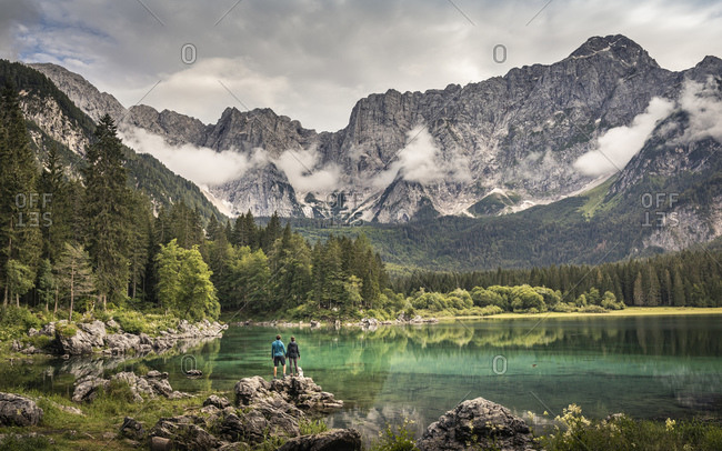 Man and woman standing by lake in mountain landscape