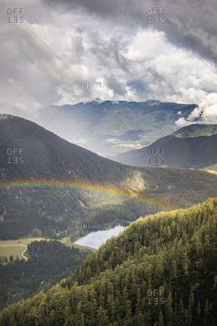 Rainbow over mountain landscape with lake