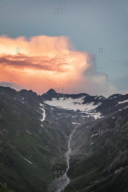 Orange sunset clouds over mountain landscape