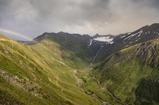 Rainbow and storm clouds over mountain and valley