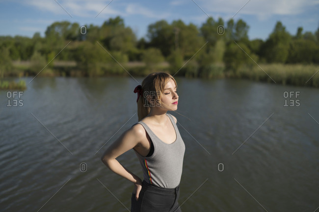 Beautiful woman standing with hands in pockets by lake