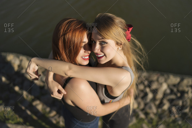 Smiling lesbian couple embracing while standing by lake