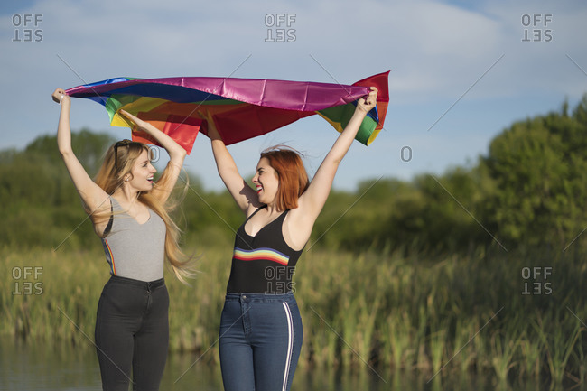 Happy lesbian couple holding rainbow flag while standing sky