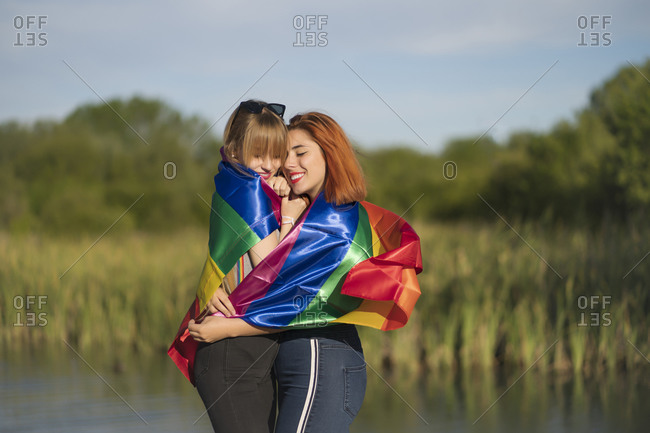 Young lesbian couple covered in rainbow flag embracing each other while standing by lake