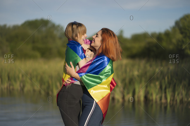 Happy young lesbian couple covered in rainbow flag embracing while standing by lake