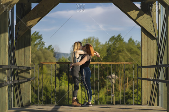 Couple kissing while standing on bridge