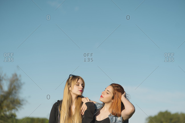 Young lesbian couple with eyes closed standing against sky