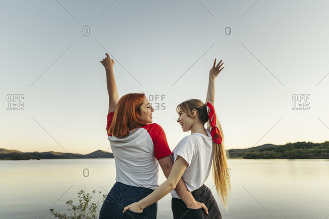 Carefree lesbian couple with hands in pockets standing against clear sky during sunset