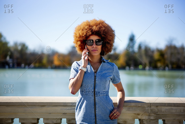 Afro hair woman wearing sunglasses talking on phone at Estanque Grande Del Retiro pond on sunny day- Spain