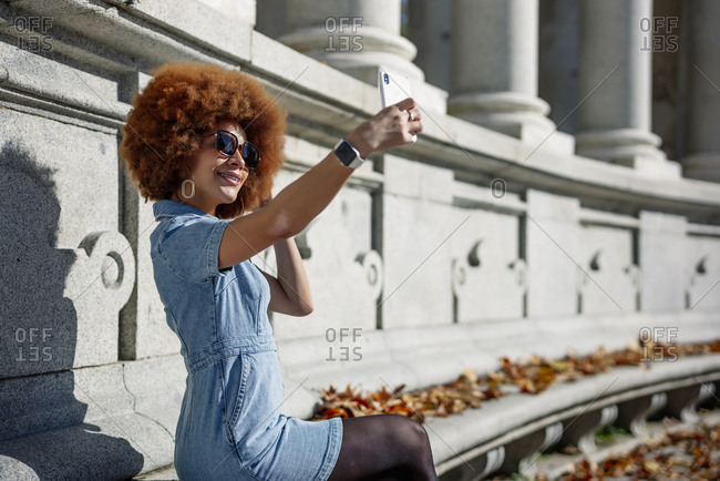 Smiling woman taking selfie at Alfonso Xii Monument on sunny day- Parque Del Buen Retiro- Spain