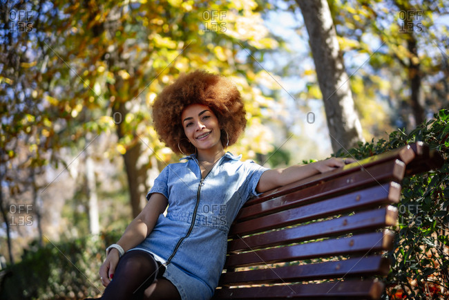 Happy woman sitting on bench at public park