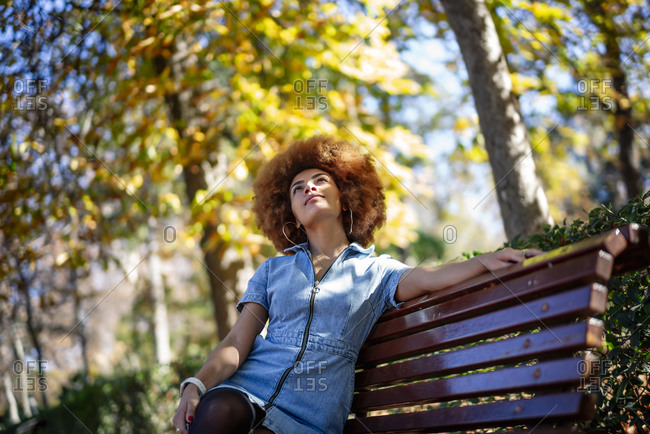 Mid adult woman looking up while day dreaming on bench at public park