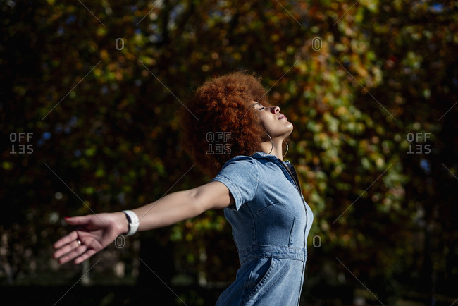 Mid adult woman with arms outstretched and eyes closed at public park