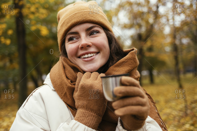 Happy young woman looking away while holding insulated cup in autumn park