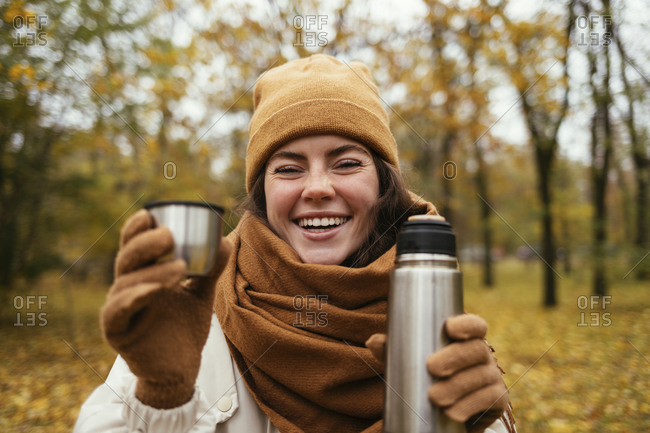 Happy woman in knit hat with stainless steel bottle at autumn park
