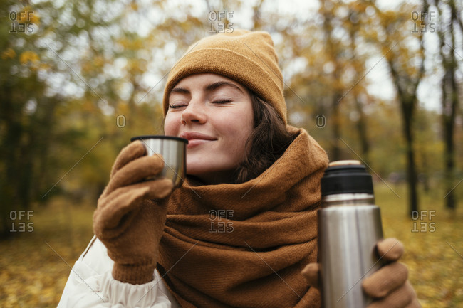 Young woman with eyes closed smelling tea in autumn park