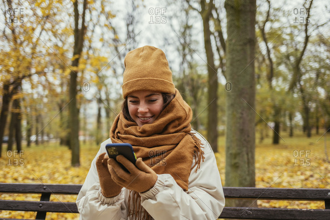 Smiling young woman using mobile phone while sitting on bench at autumn park