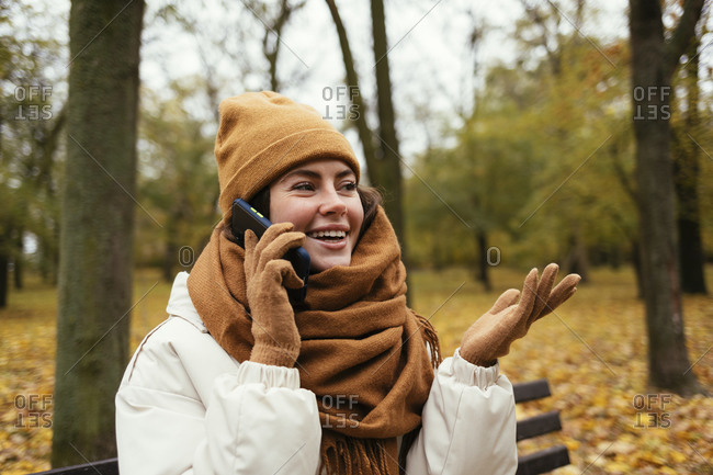 Happy young woman gesturing while talking on phone call in autumn park
