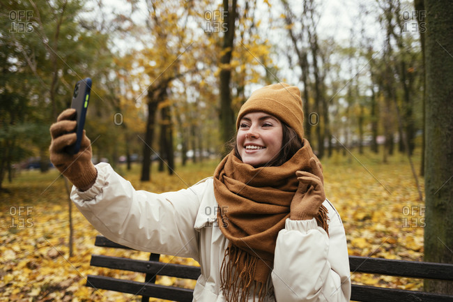 Happy young woman taking selfie while sitting on bench at autumn park