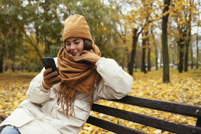 Smiling young woman with hand on chin using mobile phone in autumn park