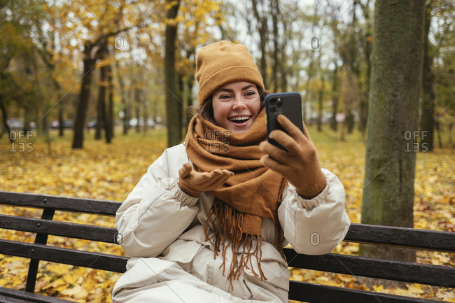 Cheerful young woman on video call while sitting on bench in autumn park