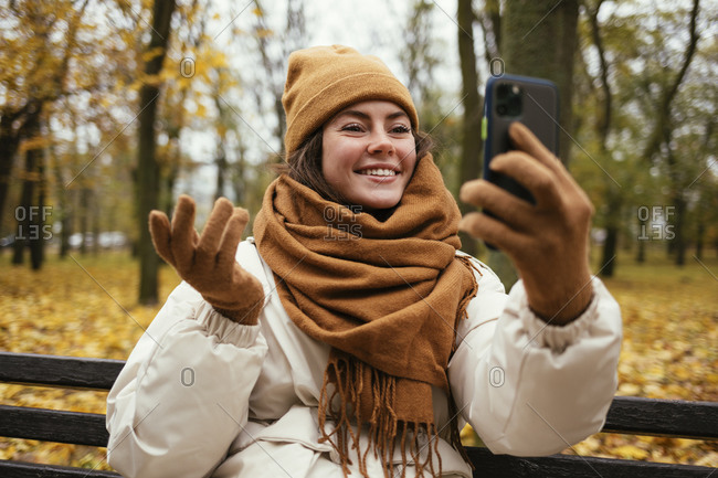 Smiling young woman hand gesturing while talking on video call in autumn park