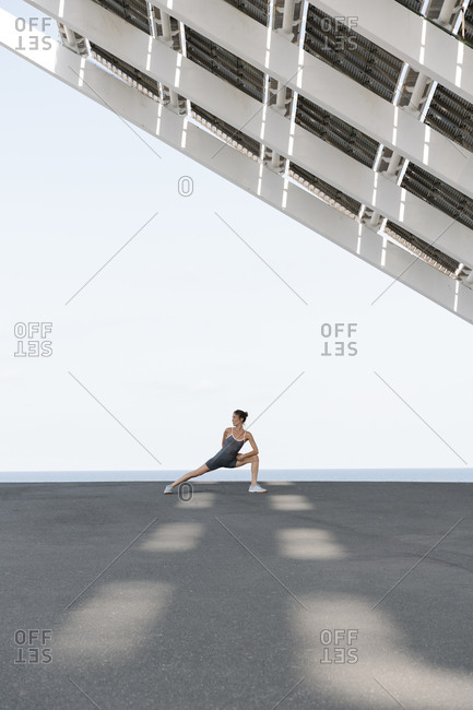 Female sportsperson stretching under built structure