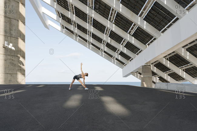 Sportswoman with hand raised practicing yoga under built structure against sky