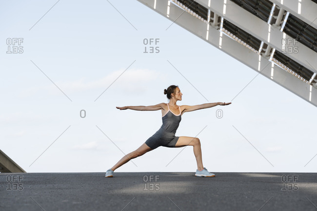 Sportswoman in warrior position against sky under built structure