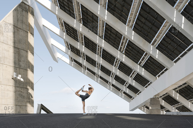 Female sportsperson doing yoga pose under built structure
