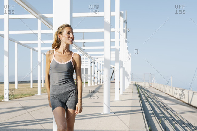 Happy sportswoman looking away while leaning on column