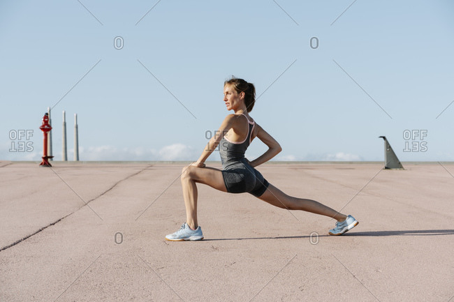 Female sportsperson doing stretching exercise on a sunny day