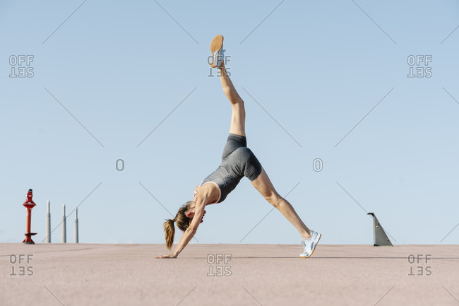 Mid adult sportswoman exercising yoga against clear sky