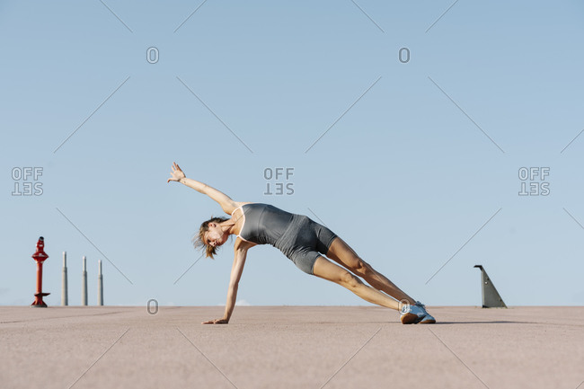 Female sportsperson practicing yoga balancing on one side