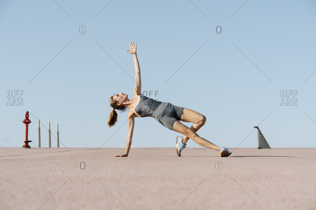 Sportswoman exercising yoga with hand raised while balancing on one side