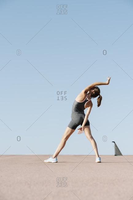 Elegant sportswoman practicing yoga on a sunny day