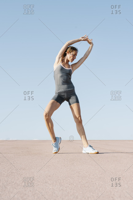 Mid adult woman stretching with hand raised