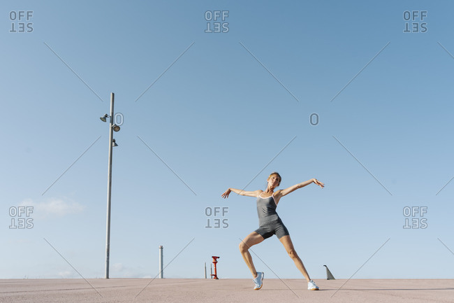 Sportswoman with arms outstretched exercising against sky