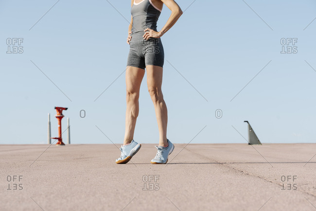 Female sportsperson with hand on hip standing on tiptoe