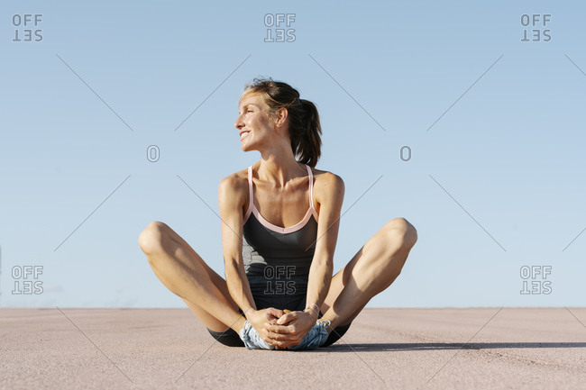 Female sportsperson looking away while sitting in cobbler pose