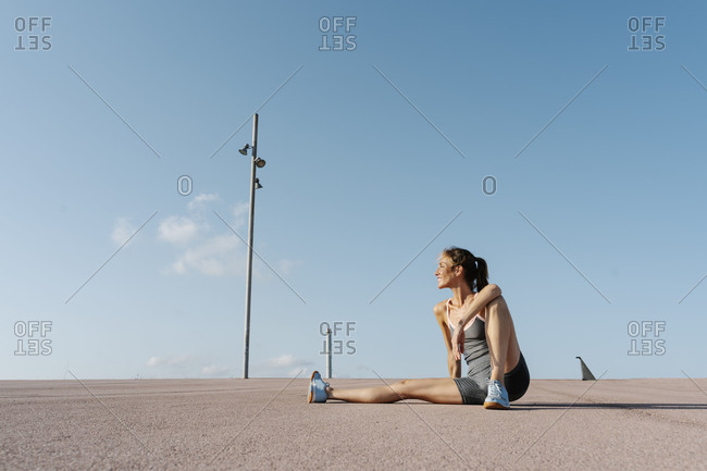 Smiling sportswoman sitting on ground- relaxing on a sunny day