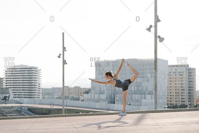 Mid adult sportswoman doing yoga pose on a sunny day
