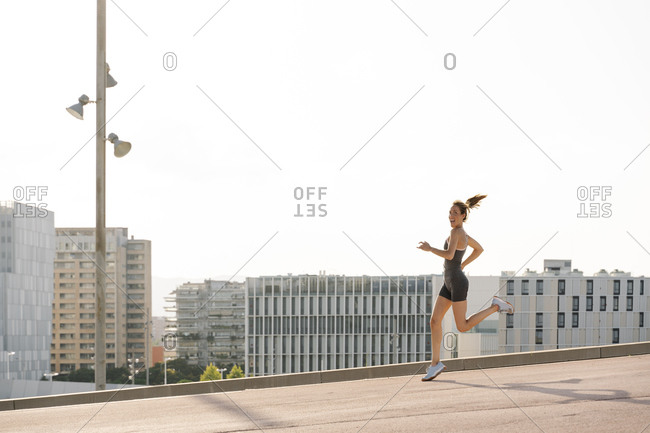 Cheerful sportswoman running on sunny day in the city