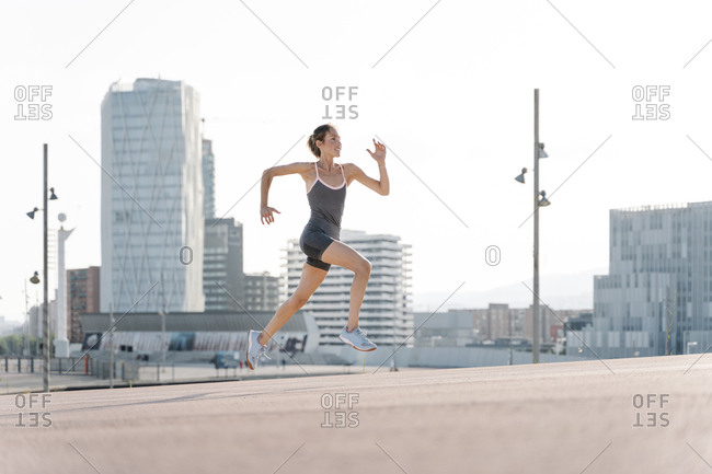 Smiling sportswoman running in in the city