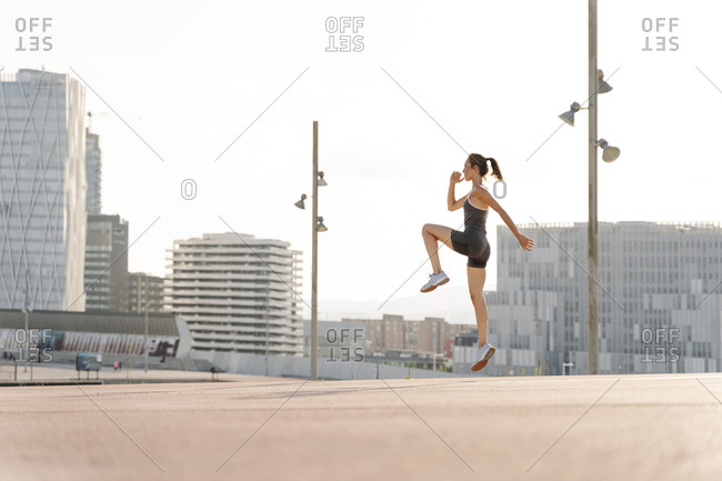 Mid adult sportswoman doing jumping exercise on a sunny day in the city