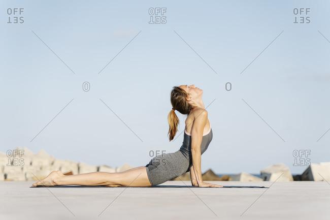 Female sportsperson doing cobra pose on exercise mat
