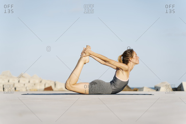 Sportswoman doing bow pose on sunny day