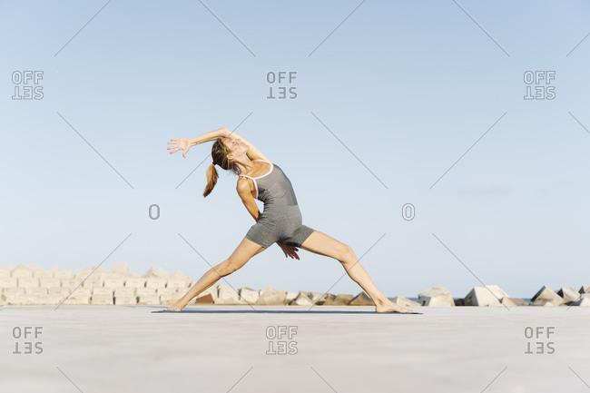 Mid adult sportswoman doing yoga on exercise mat